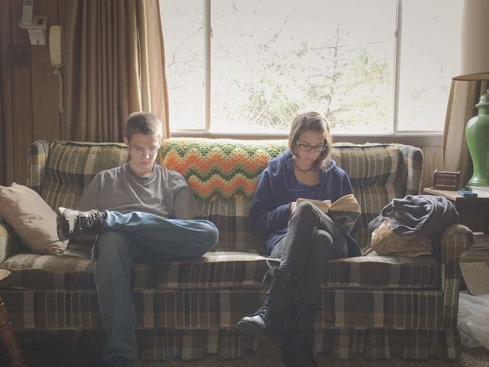 Two young adults sitting on sofa at home