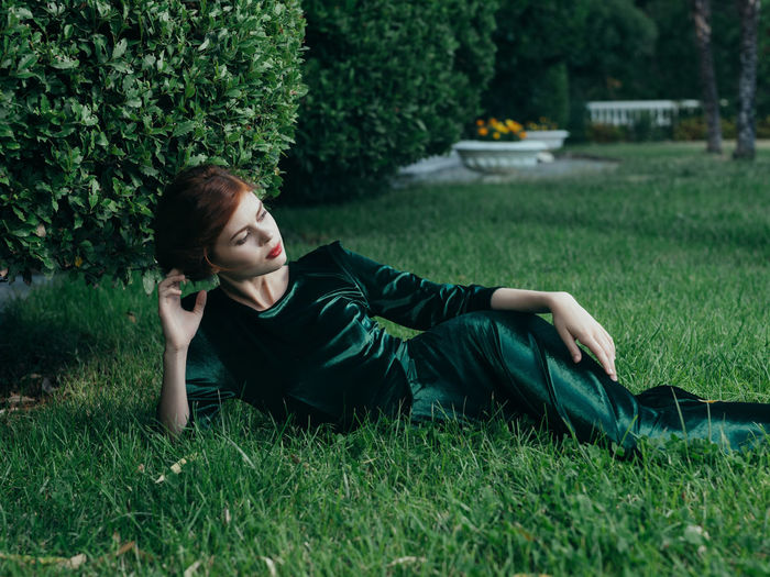 Young woman lying on grassy field