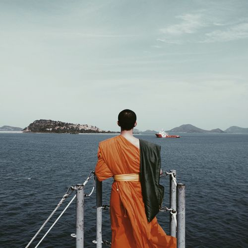 Rear view of monk looking at sea against sky