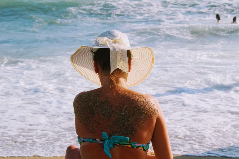 Rear View Of Mid Adult Woman Sitting At Beach