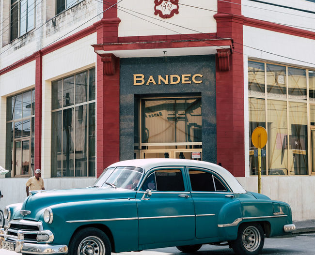 Holguín Cuba - August 2017: Classic vintage car driving in front of bank with apple sticker on window. Cuba EyeEmNewHere Retro Teal American Car Architecture Bank Building Exterior Built Structure Car Chevrolet Chevy Classic City Day Editorial  Embargo Iconic Land Vehicle Mode Of Transport No People Outdoors Text Tourism Transportation Vehicle EyeEmNewHere EyeEmNewHere