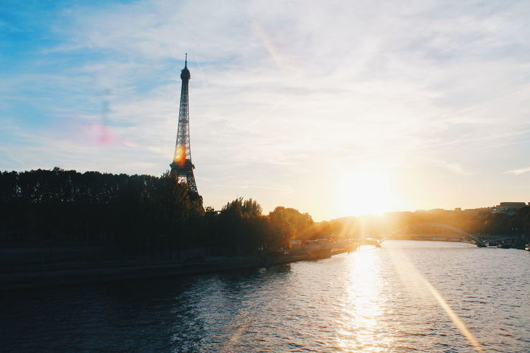 View of eiffel tower by river during sunset