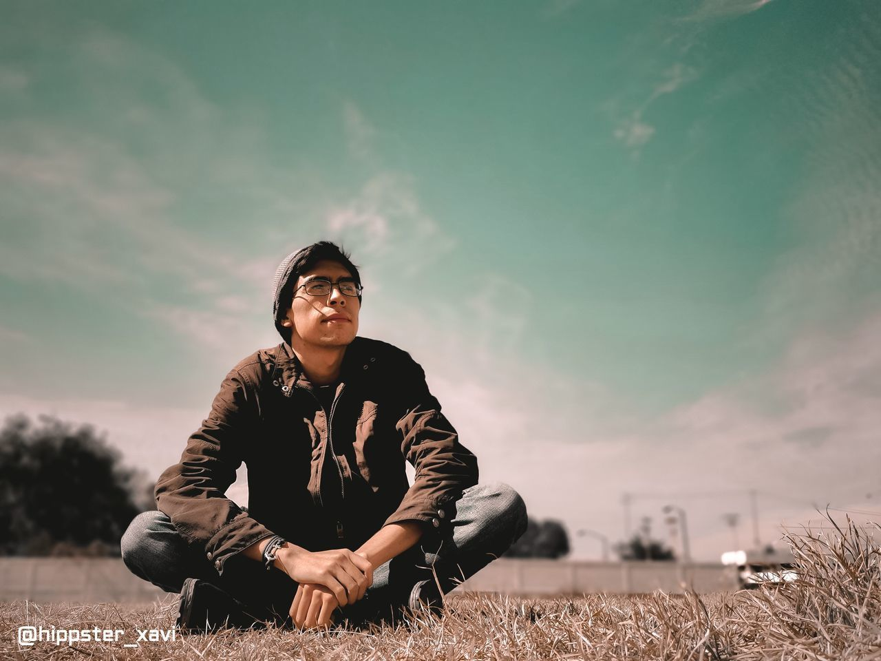 YOUNG MAN SITTING ON FIELD AGAINST SKY