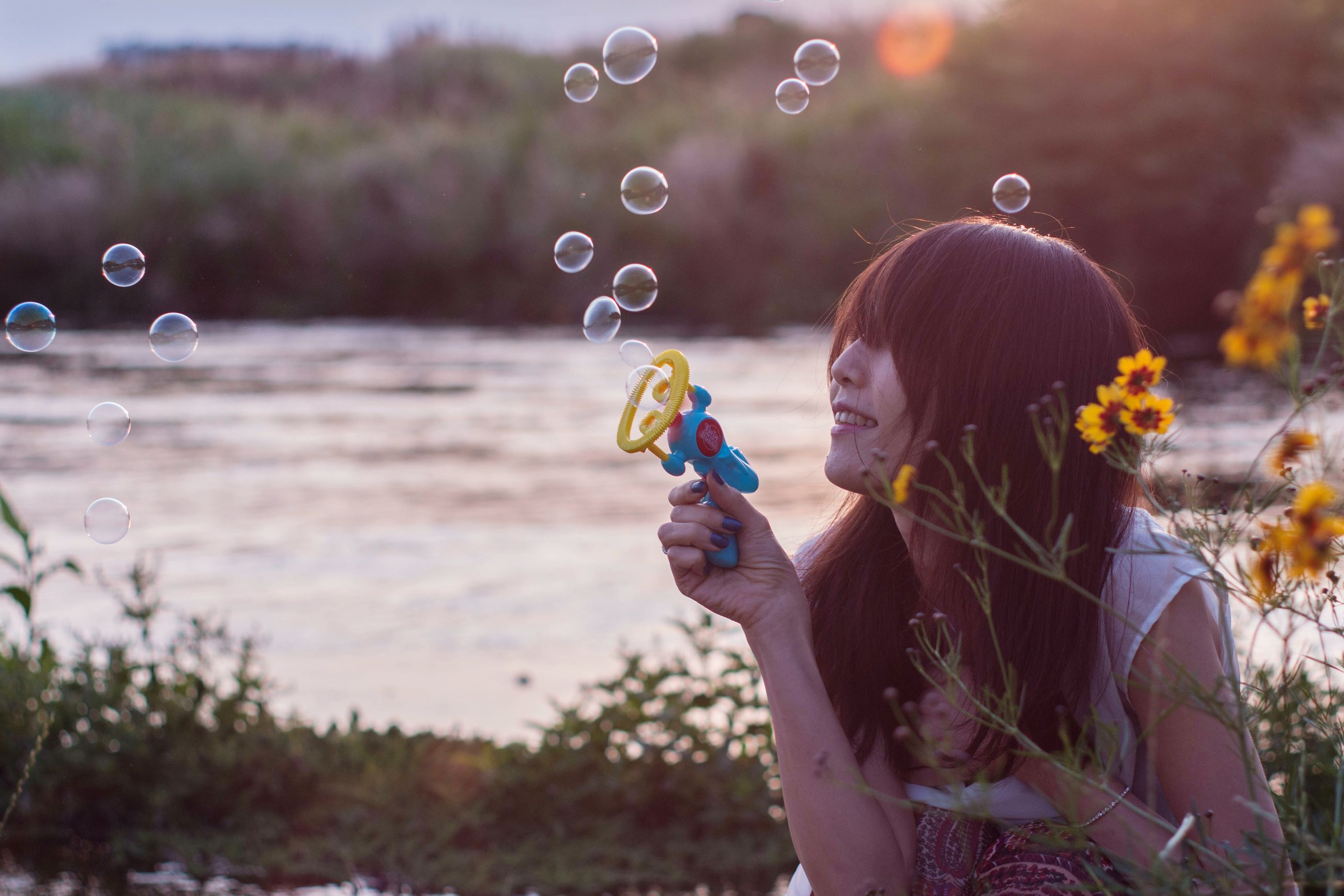 bubble wand, bubble, leisure activity, blowing, one person, focus on foreground, fragility, holding, flower, outdoors, real people, mid-air, casual clothing, day, nature, lifestyles, standing, childhood, young adult, young women, tree, people