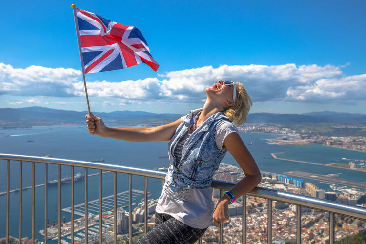 Happy woman holding british flag while leaning on railing against cityscape