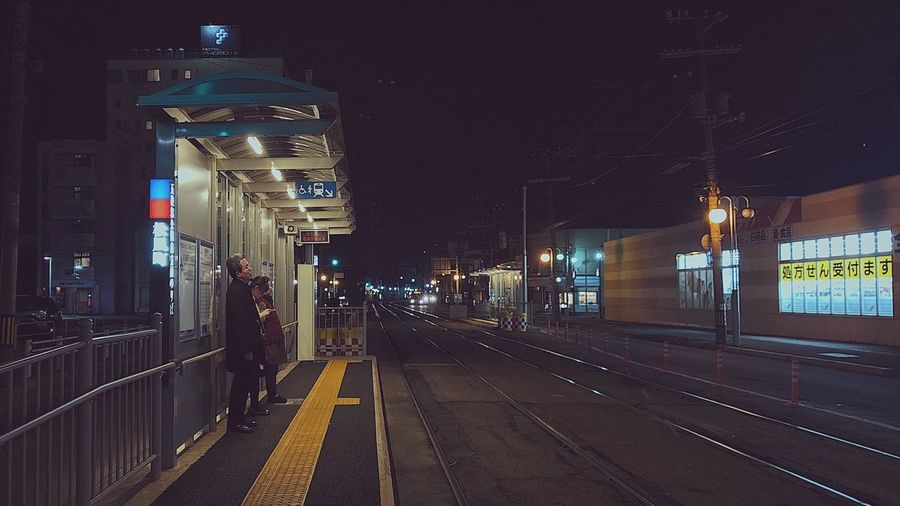 Illuminated railroad tracks in city at night
