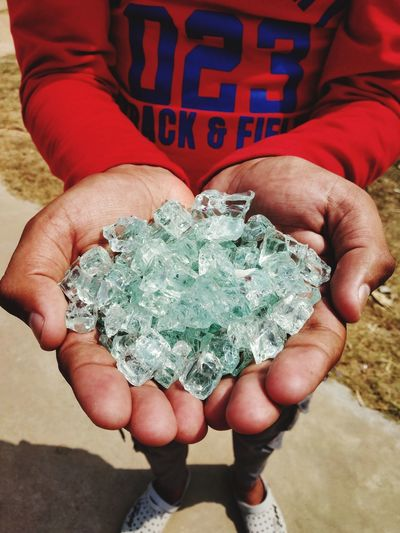 Midsection of man holding crystals in cupped hands outdoors