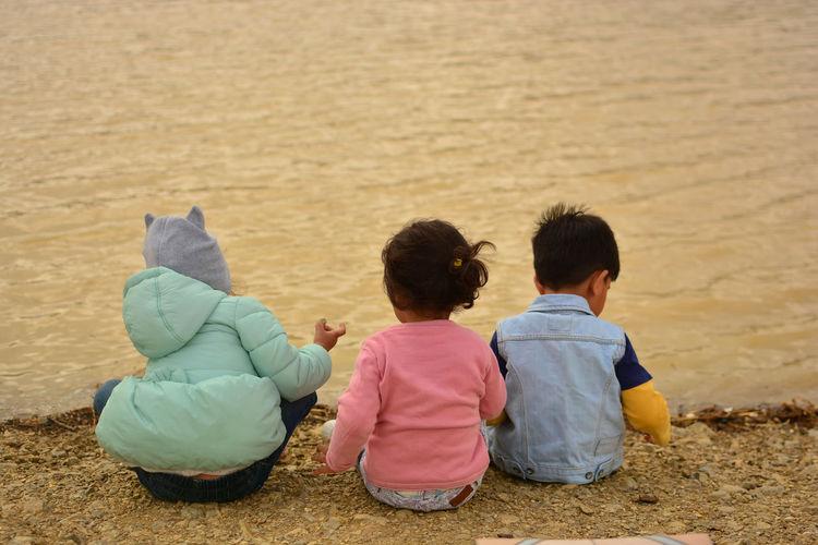 Rear view of boys sitting on beach