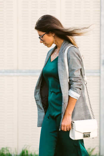 Side view of woman standing on footpath