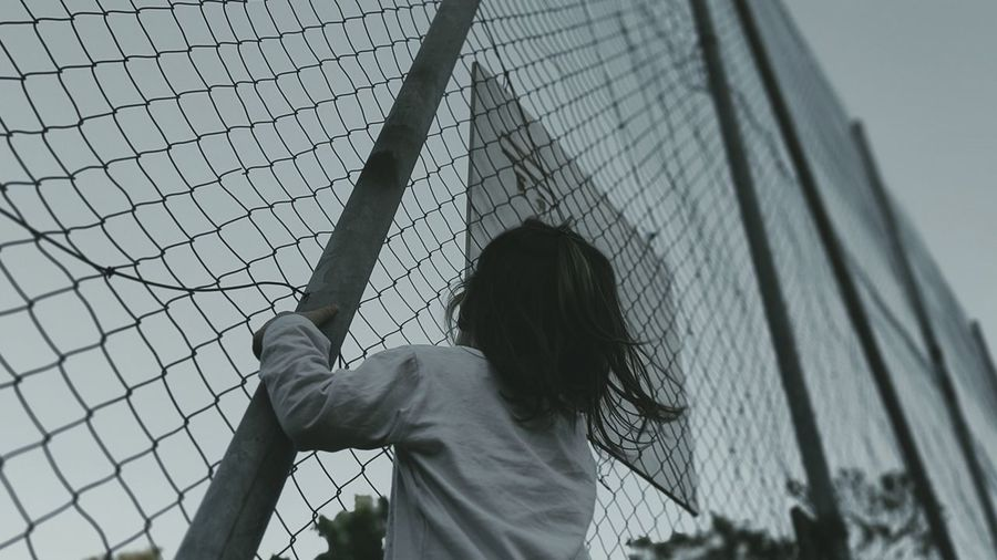 Rear view of woman standing by chainlink fence against sky
