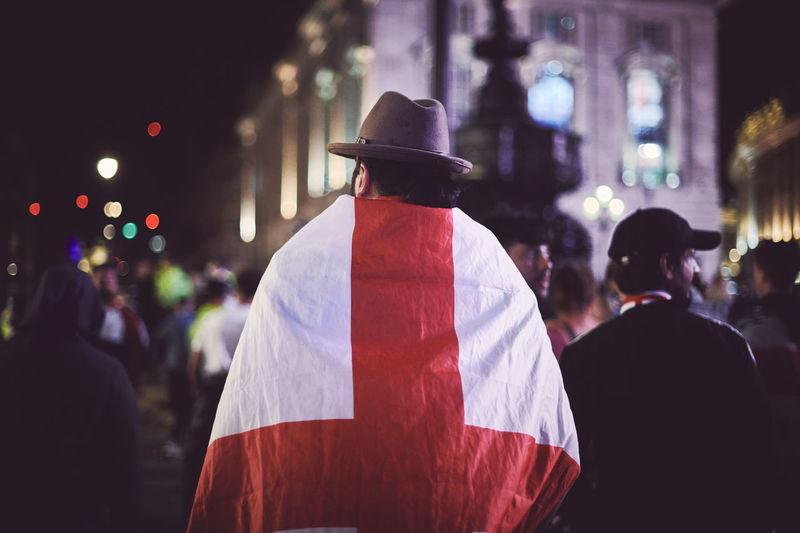 Rear view of person draped in england flag at night