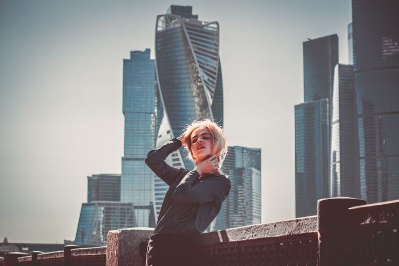 Portrait of woman standing against modern buildings in city