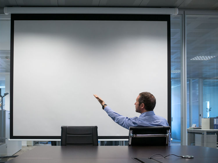 Manager explains at projection screen Business Business Finance And Industry Business Man Business Meeting Businesswear Communication Conference Room Cooperation Education Explaining  Indicate Learning Manager Office Office Life Office Man Point At Professor Projection Screen Projector Shirt Teaching Teamwork Trainer White Board