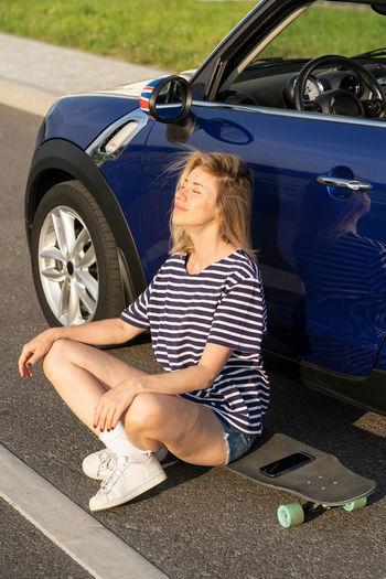 Full length of woman sitting on car