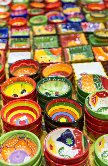 Colourful hand painted bowls and pots for sale arranged in rows on market stall. Full frame vibrant colours background vertically crop Abundance Arrangement Art Art And Craft Backgrounds Bowls Choice Clay Close-up Collection For Sale Full Frame Handmade High Angle View In A Row Large Group Of Objects Market Multi Colored Order Plates Retail  Retail Display Selective Focus Still Life Variation