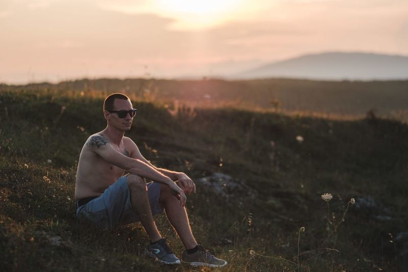 Shirtless young man sitting on field against sky during sunset