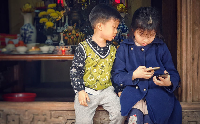 Boy sitting with sister using smart phone on railing