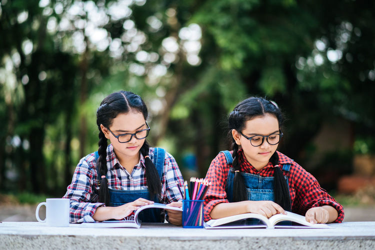 Activity Adult Book Concentration Day Education Eyeglasses  Glasses Hair Learning Looking Outdoors People Publication Reading Glasses Sitting Studying Table Togetherness Two People Women Young Adult Young Women