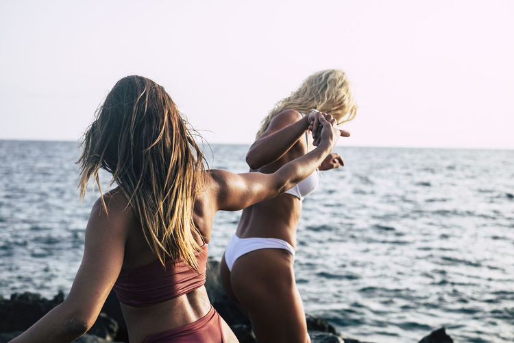 Female Friends Holding Hands While Walking At Sea Shore Against Clear Sky