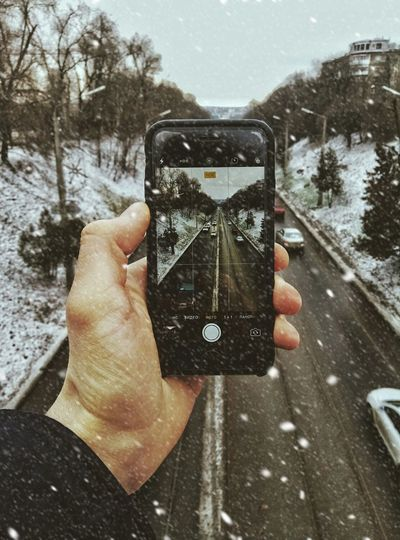 Human Hand Human Body Part Photography Themes Smart Phone Holding Wireless Technology Photographing Road Day Snow Photo Messaging Mobile Phone