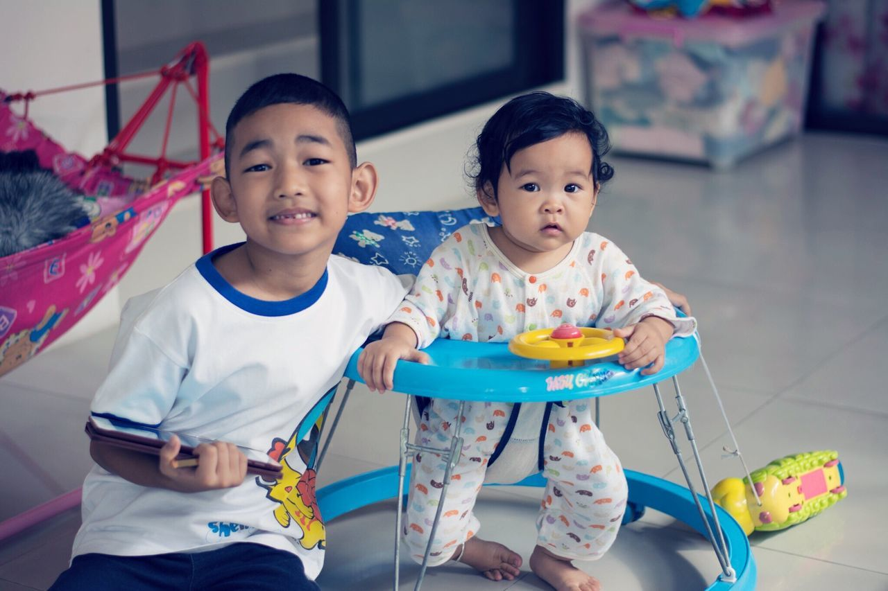childhood, boys, real people, elementary age, two people, indoors, front view, cute, focus on foreground, girls, leisure activity, lifestyles, happiness, home interior, playing, togetherness, enjoyment, looking at camera, casual clothing, sitting, smiling, portrait, day