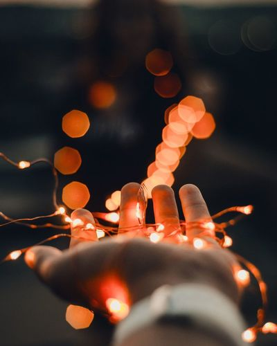 The lights in the hand Lights Light Fire Hand Bokeh Backgrounds Illuminated Night No People Close-up Focus On Foreground Celebration Indoors  Holiday Decoration Lighting Equipment Glowing Creativity Nature Christmas Lights Spirituality Christmas Religion Table Belief