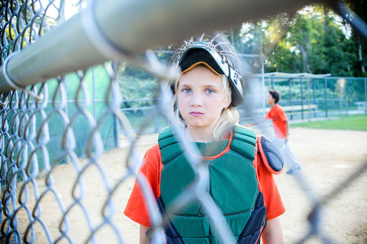 Portrait of girl standing at playing field seen through chainlink fence