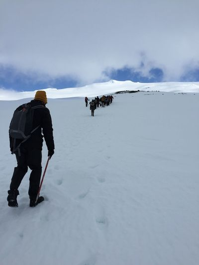 Rear view of hikers climbing uphill against cloudy sky