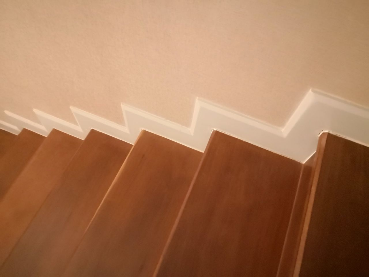 LOW ANGLE VIEW OF STAIRCASE AGAINST WALL