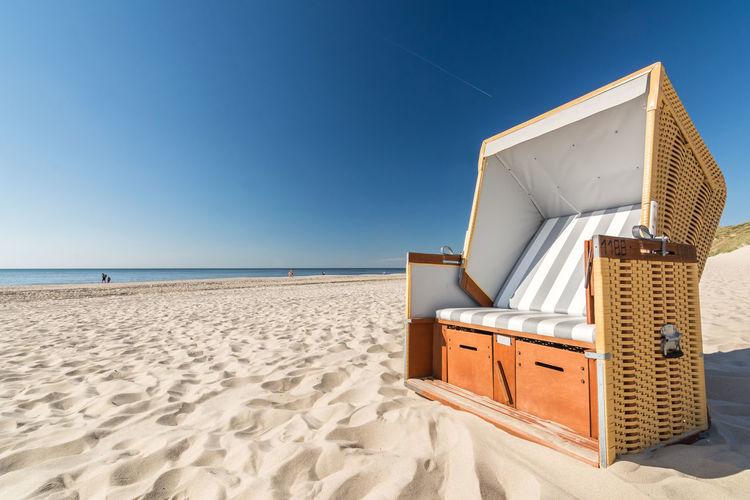 Hooded beach chair at beach against clear blue sky