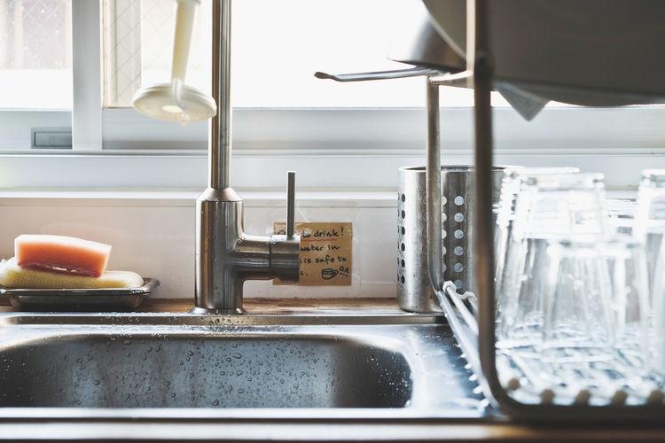 Close-up of kitchen sink against window