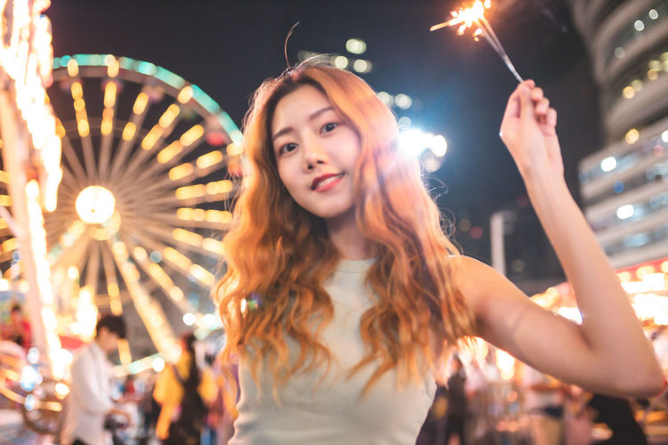 Portrait of young woman with arms outstretched at night