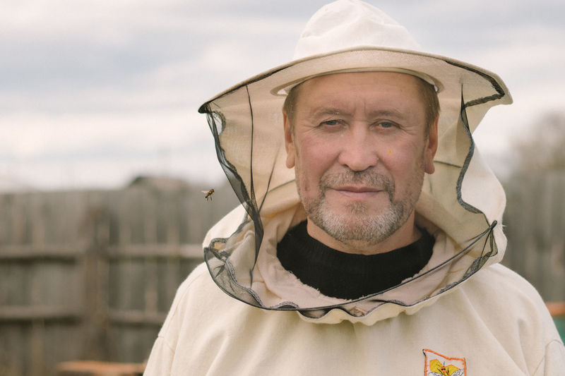Closeup portrait of a beekeeper in mask with a bee
