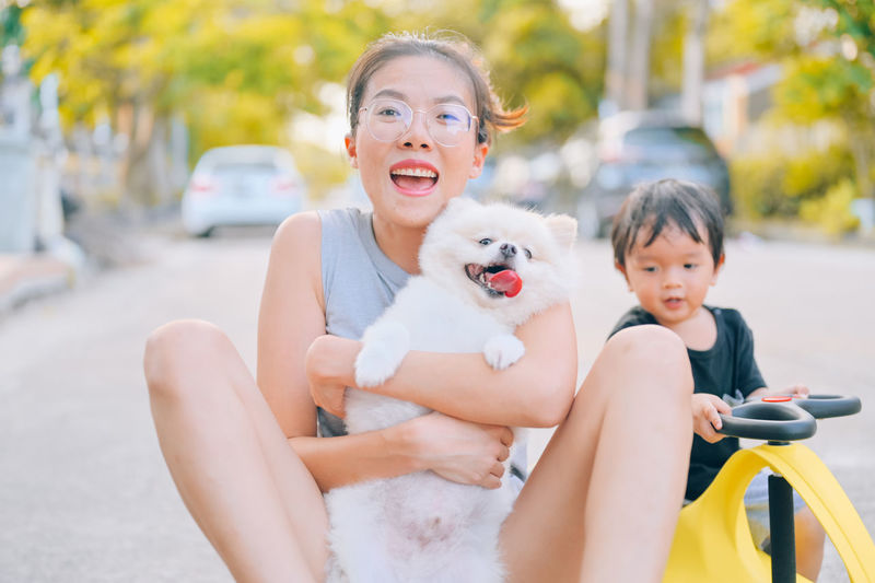Portrait of smiling woman with dog sitting outdoors