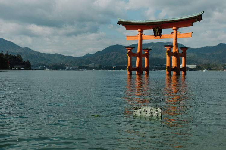 The iconic Miyajima torii Architecture Beauty In Nature Built Structure Cloud - Sky Cloudy Hiroshima Inari Itsukushima Shrine Japan Japanese  Japanese Culture Lake Miyajima Mountain Mountain Range No People Outdoors Religion Scenics TORII Tranquil Scene Tranquility Travel Travel Destinations Water