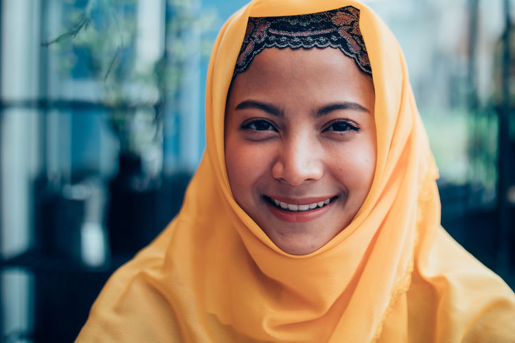 Portrait Headshot Real People Looking At Camera Smiling Lifestyles Front View One Person Focus On Foreground Casual Clothing Happiness Leisure Activity Young Adult Young Women Traditional Clothing Women Hijab Headscarf Beautiful Woman Scarf
