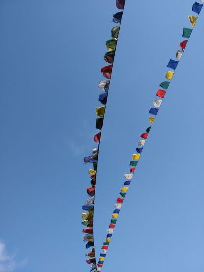 Low angle view of prayer flags against sky on sunny day