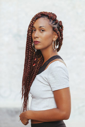 Portrait of young woman with braided hair against white background