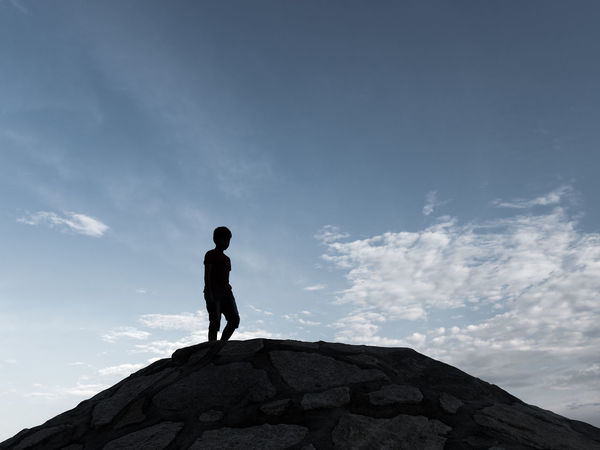 Silhouette of a boy walking on rocky groyne under evening sky Sky One Person Standing Real People Leisure Activity Rock Cloud - Sky Beauty In Nature Silhouette Outdoors Low Angle View People Kid Boy Walking Blue Sky Evening Sky Groyne Groin Playing Clouds