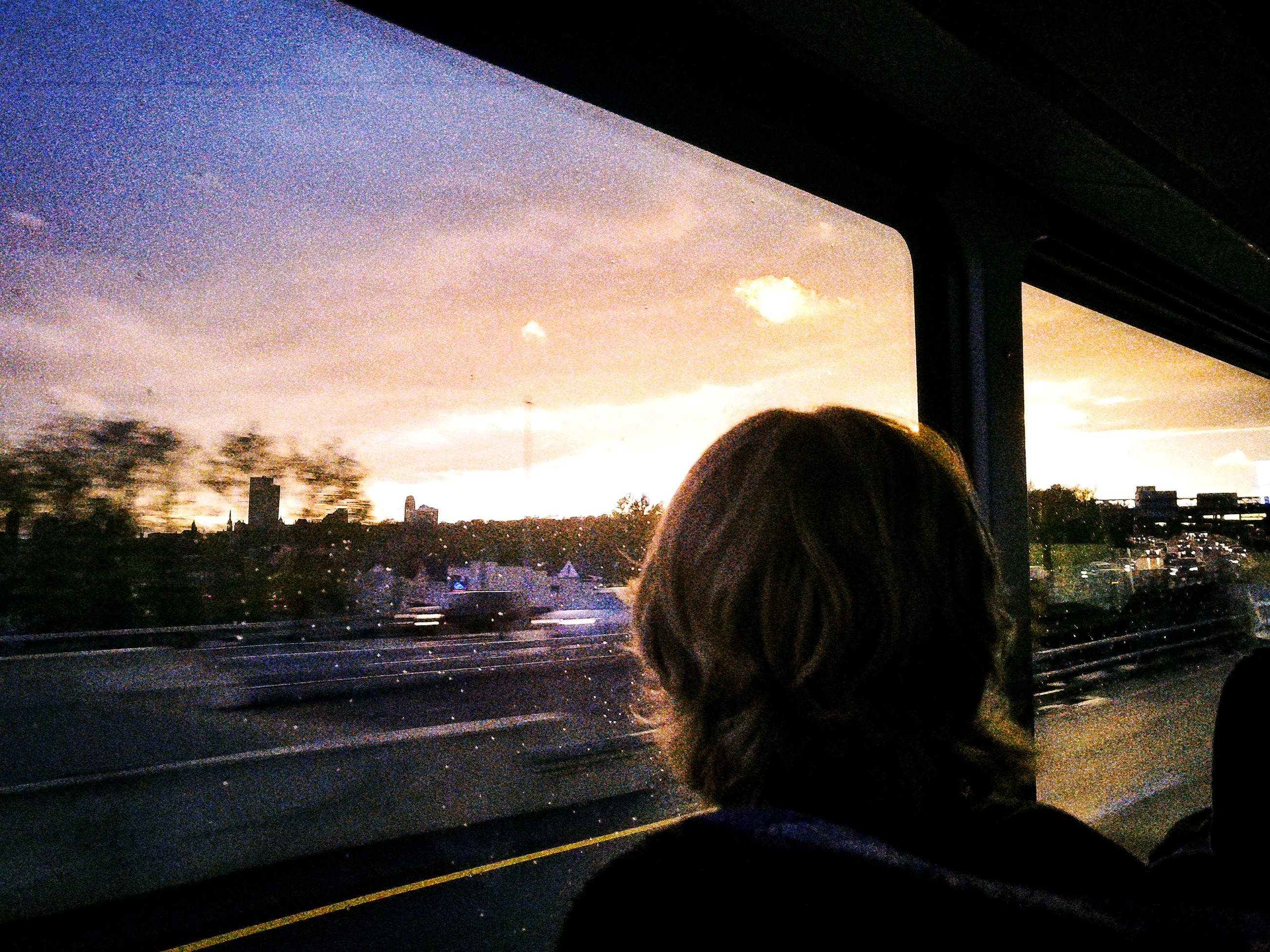 sky, transportation, rear view, headshot, transparent, glass - material, vehicle interior, cloud - sky, car, mode of transportation, one person, road, sunset, motor vehicle, nature, architecture, land vehicle, window, real people, portrait, outdoors