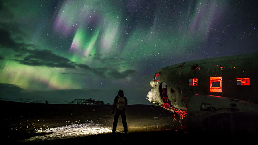 Person standing by abandoned airplane at solheimasandur beach against sky with aurora borealis at night