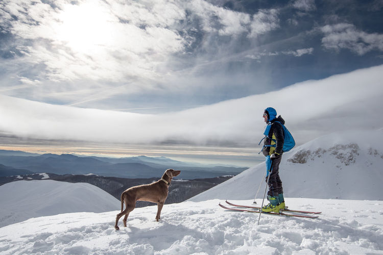 Man with dog snowboarding on snowcapped mountain against sky