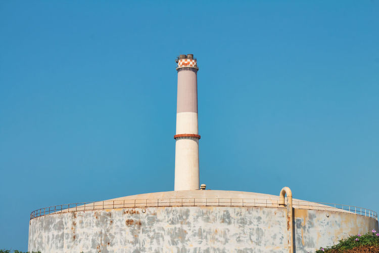 Low angle view of chimney against clear blue sky