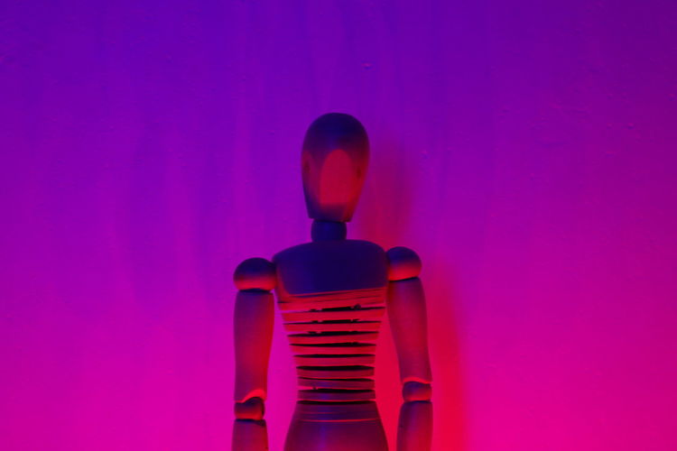 Close-Up Of Wooden Figurine Against Purple Wall