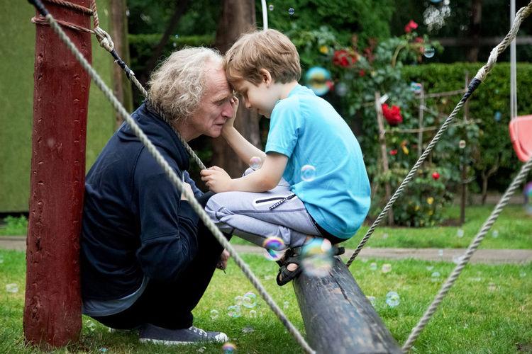 Mature man and grandson crouching in playground