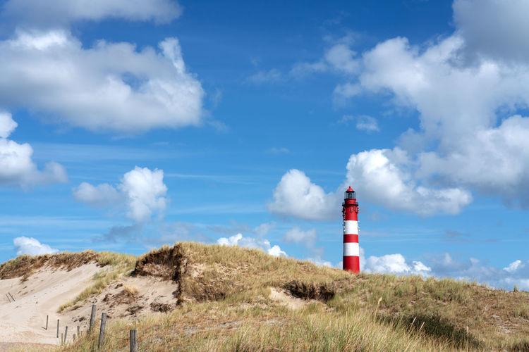 Lighthouse on field against cloudy sky