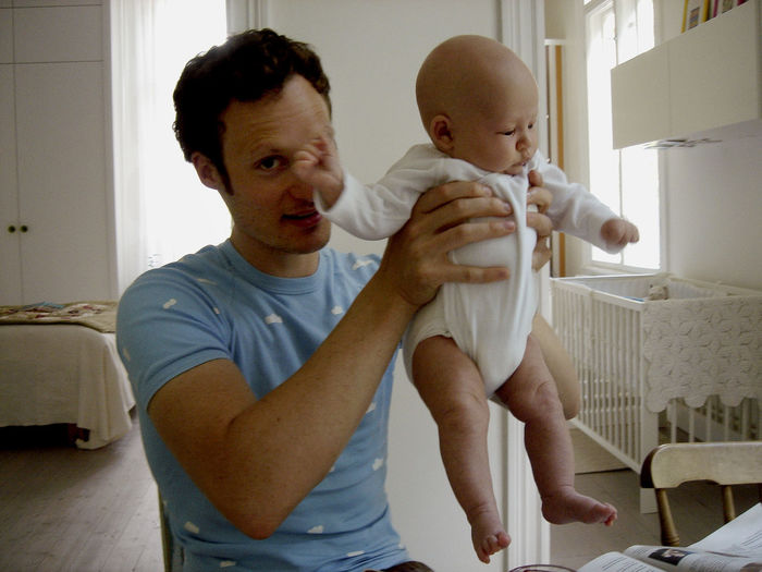 Father lifting baby girl at home