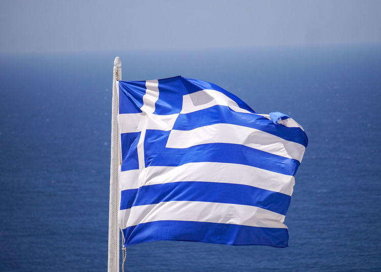 Close-up of greek flag against seascape