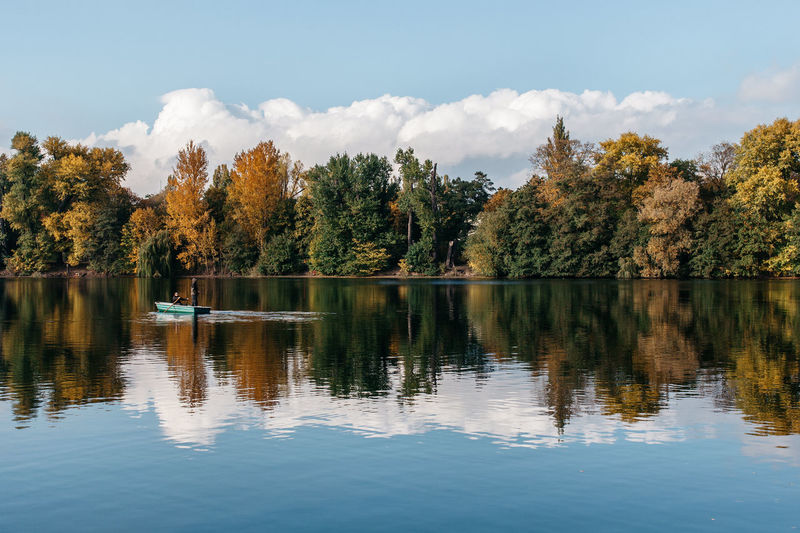 People rowing boat in lake by trees against sky during autumn
