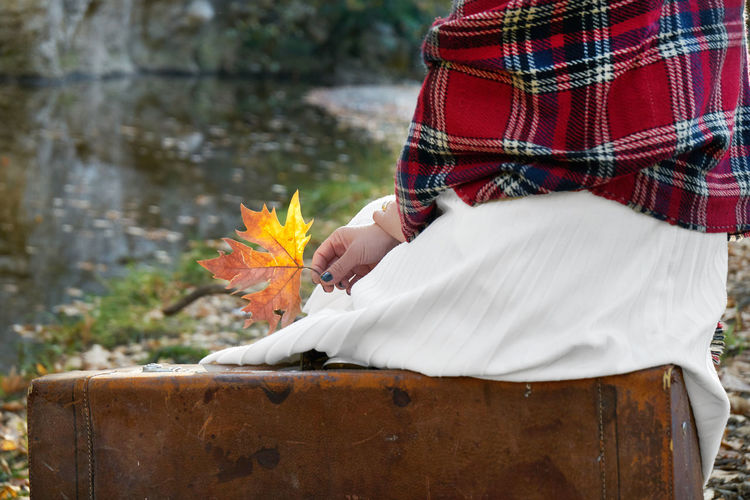 Low section of woman holding autumn leaf
